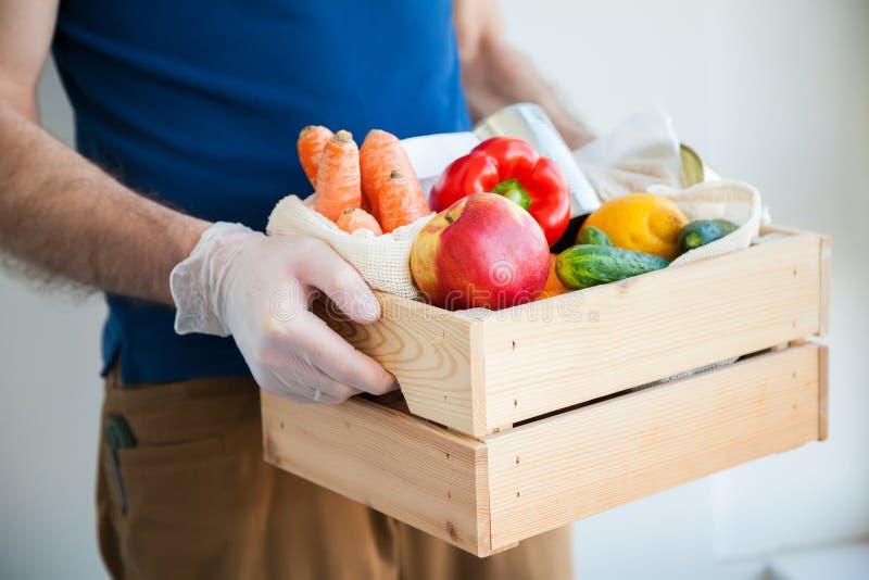 Manos en guantes sosteniendo caja de alimentos fotos de archivo libres de regalías