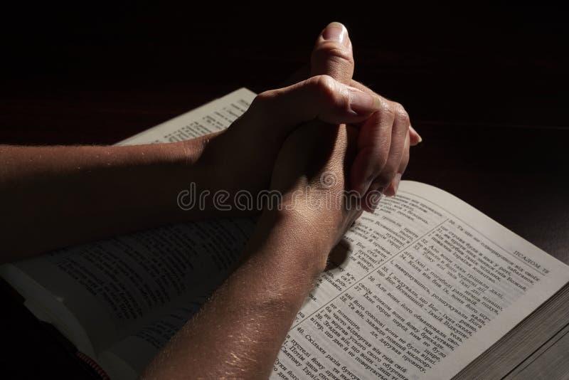 Manos en la biblia foto de archivo