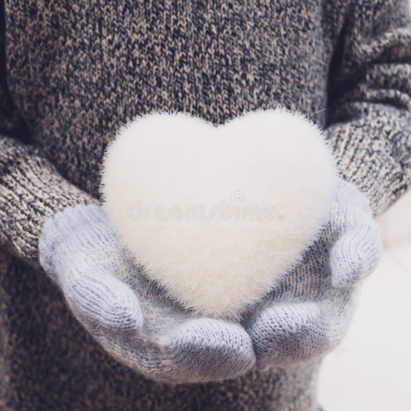 manos en las manoplas hechas punto que llevan a cabo el corazón blanco imagen de archivo libre de regalías