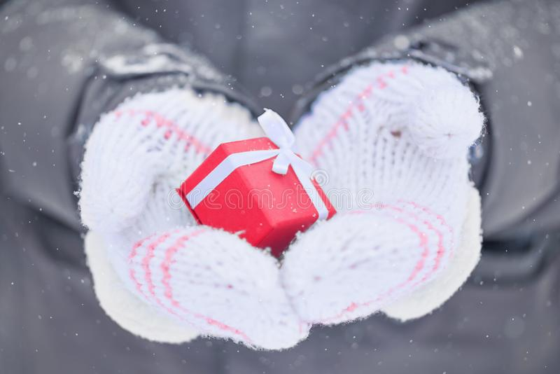 Manos en las manoplas que llevan a cabo un presente en una caja fotografía de archivo libre de regalías