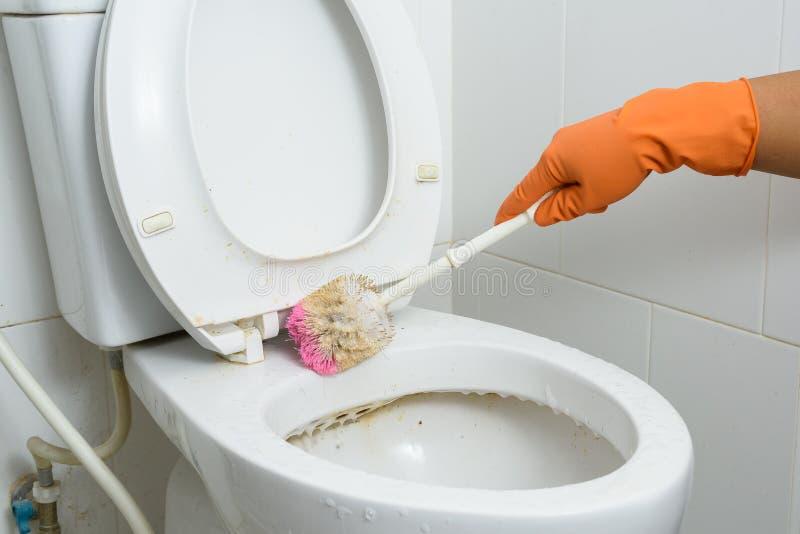 Manos en los guantes anaranjados que limpian WC, retrete, servicio usando cepillo imágenes de archivo libres de regalías