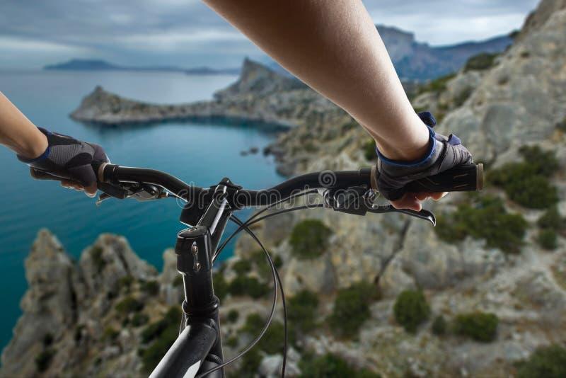 Manos en los guantes que sostienen el manillar de una bicicleta Ciclista de la bici de montaña que monta la sola pista El hacer a foto de archivo libre de regalías