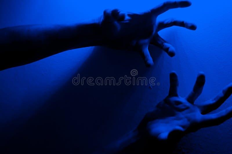 Manos en luz de neón de contraste azul monocromo Hombre mostrando el signo del gesto de la palma de mano Fotografía artística imagen de archivo