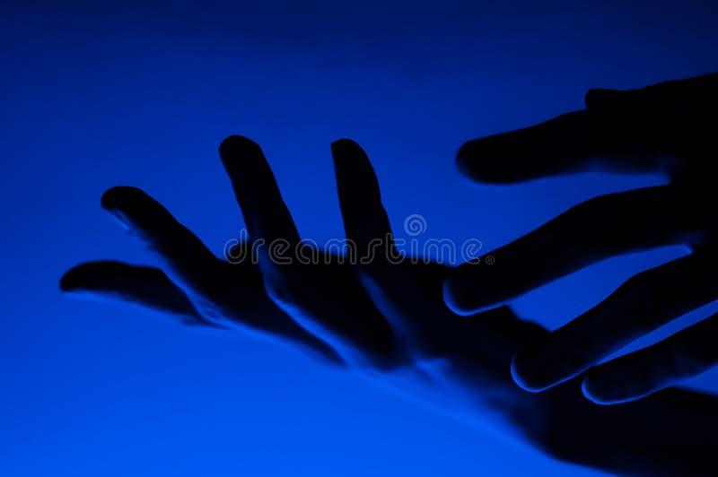 Manos en luz de neón de contraste azul monocromo Hombre mostrando el signo del gesto de la palma de mano Fotografía artística fotografía de archivo libre de regalías
