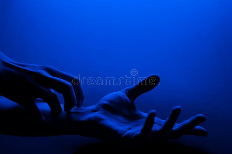 Manos en luz de neón de contraste azul monocromo Hombre mostrando el signo del gesto de la palma de mano Fotografía artística foto de archivo