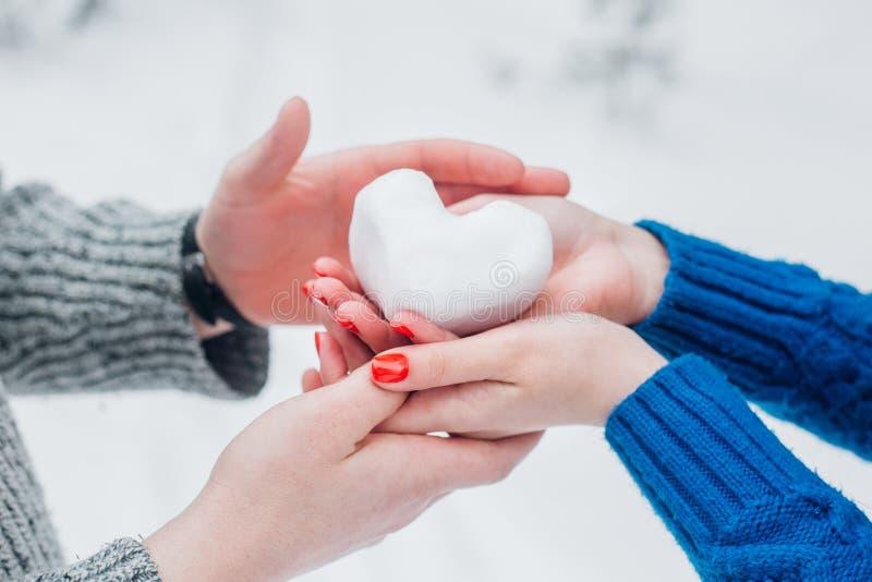 Manos en manoplas hechas punto con el corazón de la nieve en día de invierno Concepto del amor Fondo del día de tarjeta del día d fotos de archivo libres de regalías