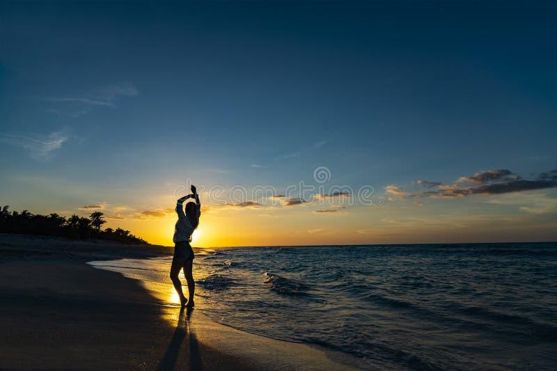 Manos encima de la mujer que presenta en la playa con el cielo hermoso de la puesta del sol, fondo de las nubes Espacio libre par imagen de archivo