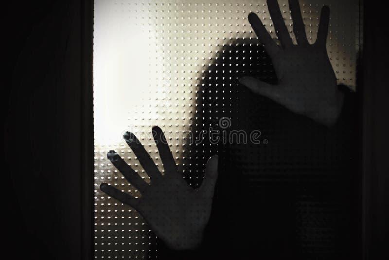 Manos espeluznantes de los fantasmas en la puerta fotos de archivo