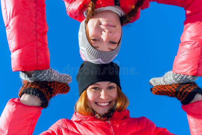 Manos felices jovenes del control de la muchacha del retrato dos al aire libre en un fondo del cielo azul en parque del invierno  foto de archivo