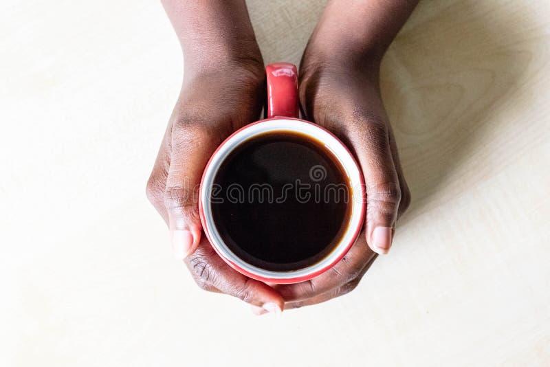Manos femeninas afroamericanas que sostienen la taza roja de café express o de capuchino del café encendido en encimera de la coc foto de archivo