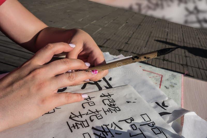 Manos femeninas chinas que escriben caligrafía china imagen de archivo libre de regalías