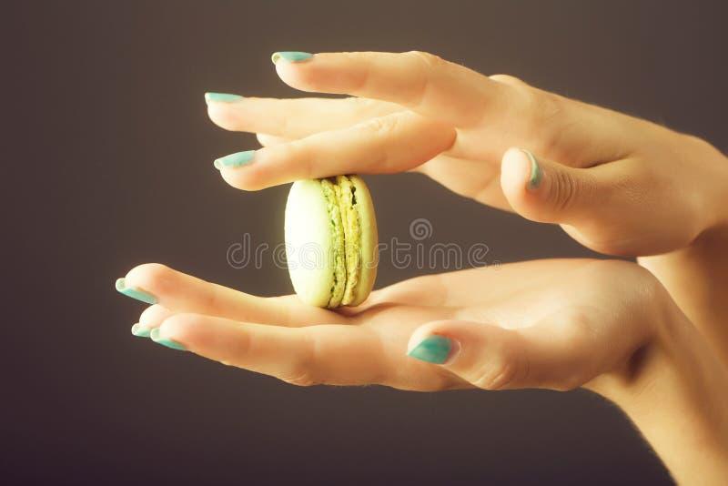Manos femeninas con el macaron imagen de archivo libre de regalías