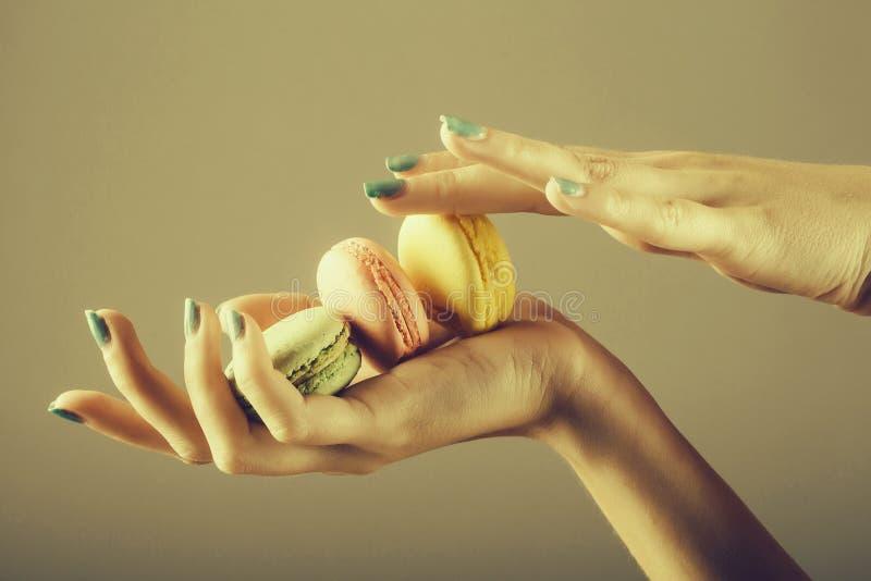 Manos femeninas con el macaron fotos de archivo libres de regalías