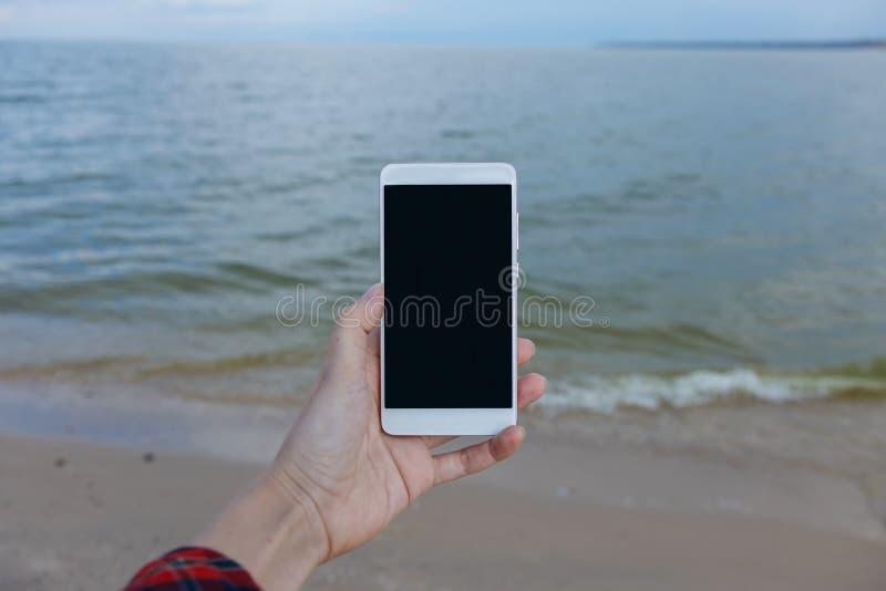 Manos femeninas con el teléfono elegante que toma las imágenes del mar foto de archivo libre de regalías