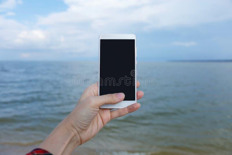 Manos femeninas con el teléfono elegante que toma las imágenes del mar imagenes de archivo