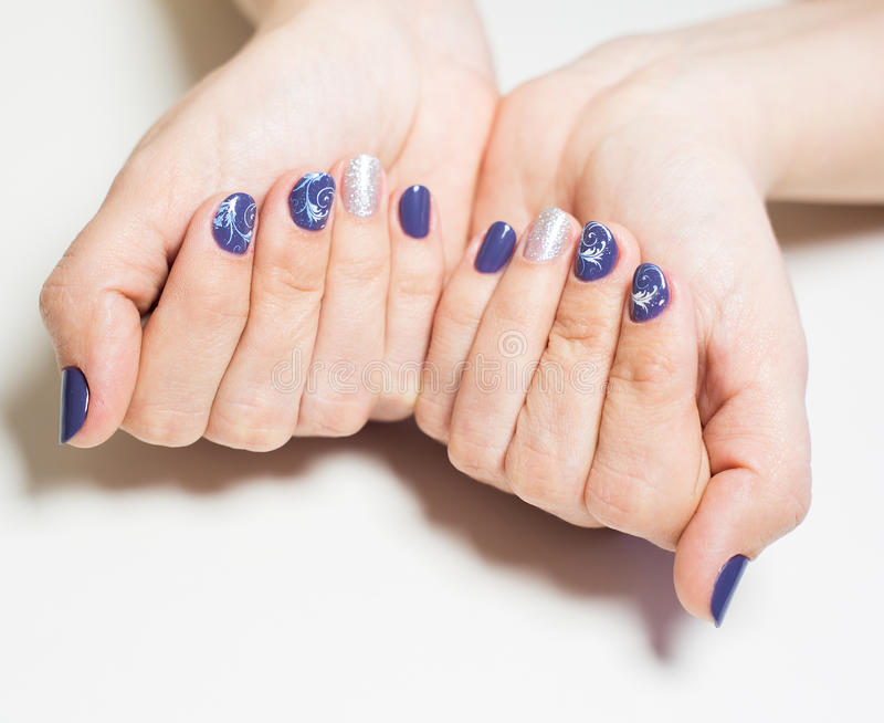 Manos femeninas con la manicura azul y de plata profesional imagenes de archivo