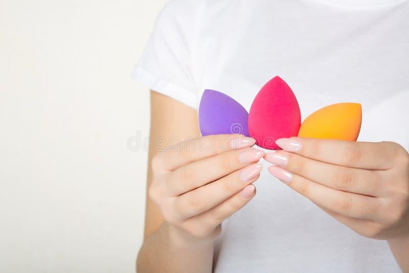Manos femeninas con la manicura bonita que se considera púrpura, el rosa y las esponjas cosméticas anaranjadas Espacio para el te fotos de archivo libres de regalías