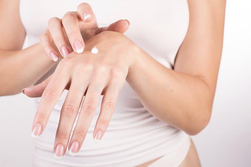 Manos femeninas con la manicura francesa que aplica la crema de la mano, fondo blanco, primer, vista delantera foto de archivo