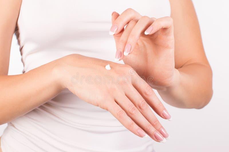 Manos femeninas con la manicura francesa que aplica la crema de la mano, fondo blanco, primer, vista delantera fotografía de archivo libre de regalías