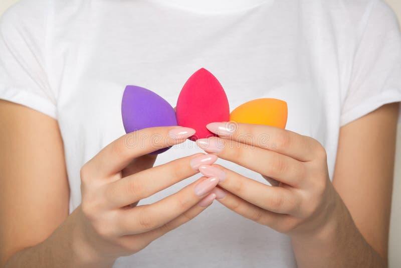 Manos femeninas con la manicura hermosa que se considera púrpura, el rosa y las licuadoras anaranjadas de la belleza fotos de archivo