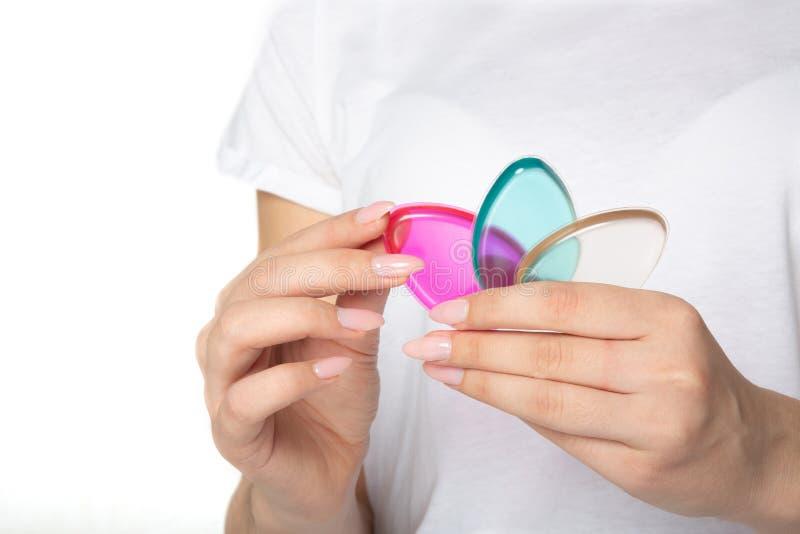 Manos femeninas con la manicura hermosa que sostiene esponjas coloridas del silicón Espacio vacío fotos de archivo libres de regalías