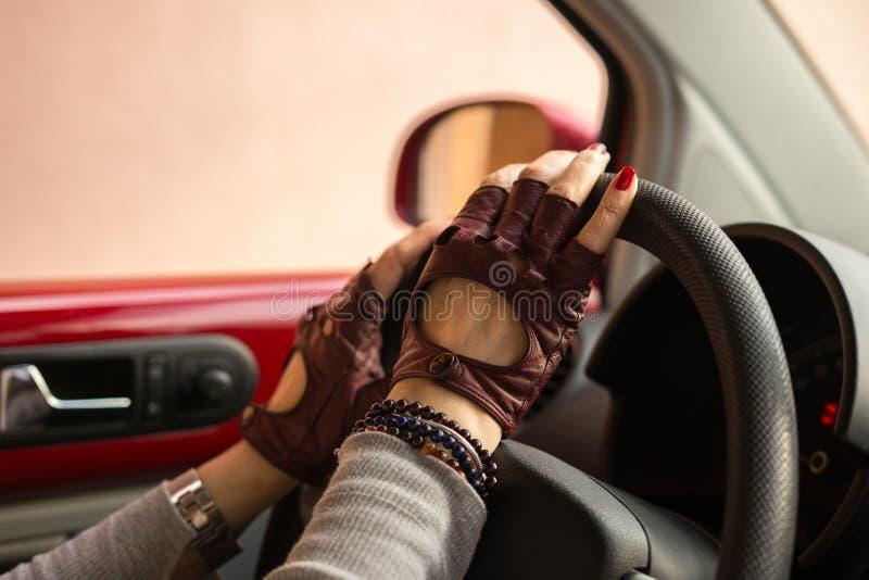 Manos femeninas con las máquinas del volante del conductor de los guantes fotos de archivo libres de regalías