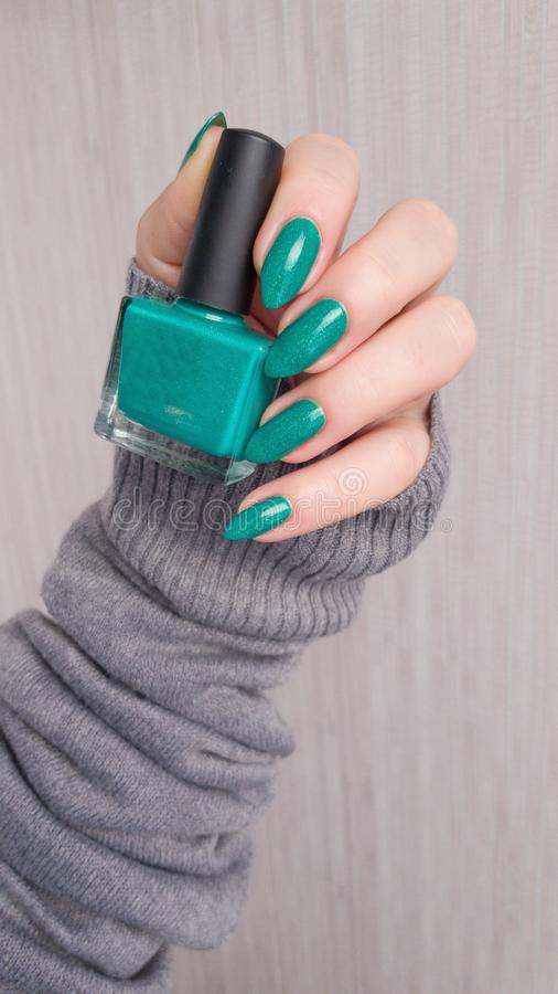 Manos femeninas con los clavos largos con el esmalte de uñas verde imágenes de archivo libres de regalías