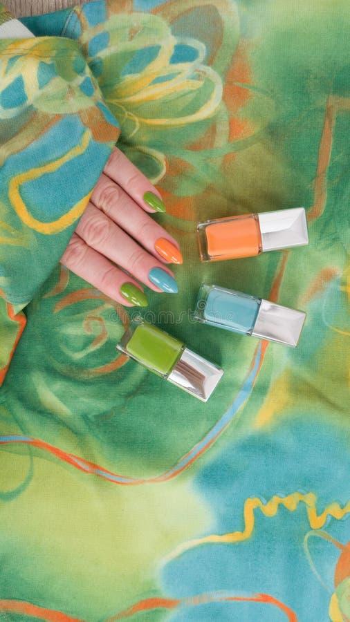 Manos femeninas con los clavos largos con el esmalte de uñas verde fotos de archivo libres de regalías