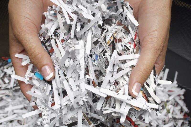 Manos femeninas con los papeles destrozados imagenes de archivo