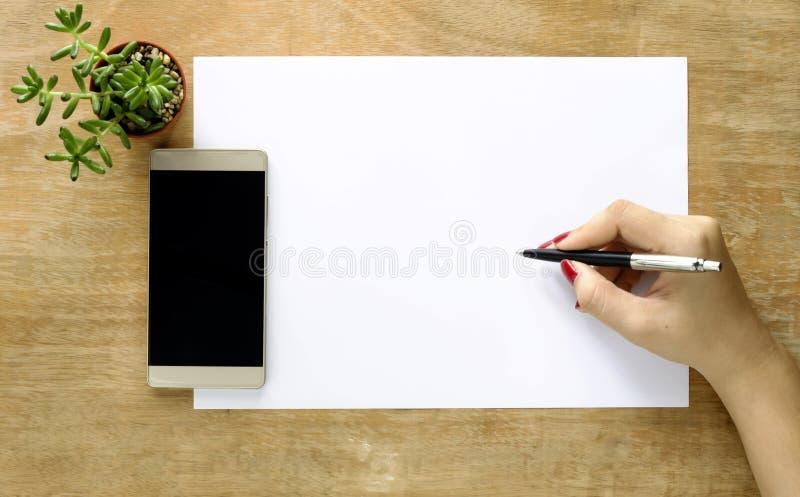 Manos femeninas con un cuaderno y una pluma, teléfonos y árbol en la tabla imagenes de archivo
