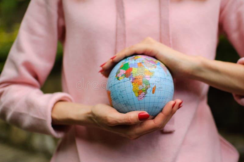 Manos femeninas con un pequeño globo con nombres ucranianos y letras cirílicas en él El continente africano es visible imagen de archivo libre de regalías