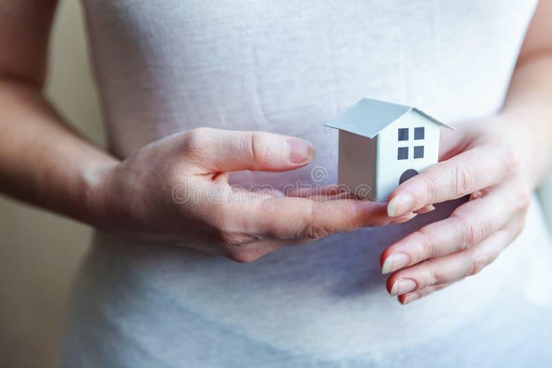 Manos femeninas de la mujer que sostienen la casa blanca miniatura del juguete imagenes de archivo
