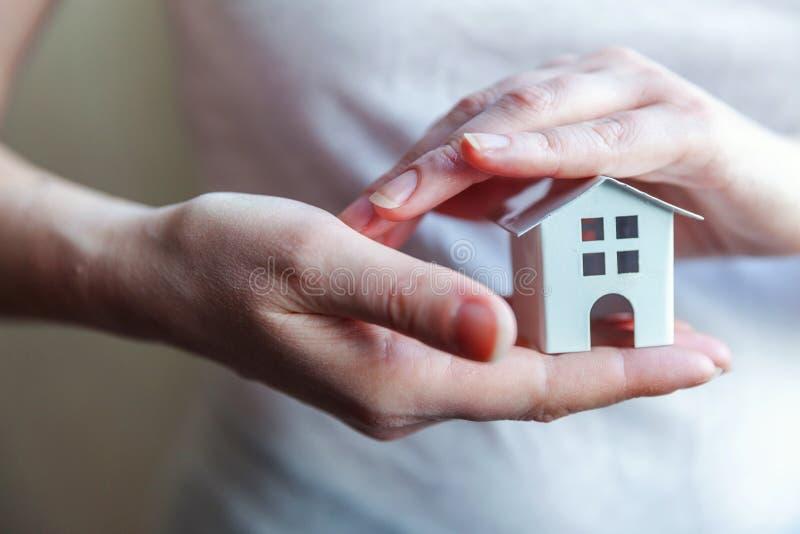 Manos femeninas de la mujer que sostienen la casa blanca miniatura del juguete fotos de archivo libres de regalías