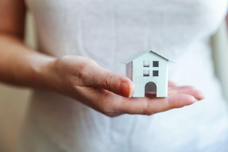 Manos femeninas de la mujer que sostienen la casa blanca miniatura del juguete foto de archivo libre de regalías