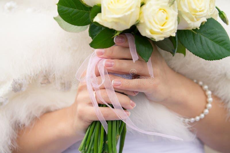 Manos femeninas de la novia que sostienen el ramo de la boda fotos de archivo libres de regalías