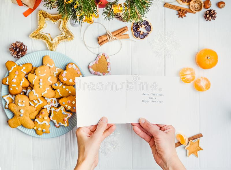 Manos femeninas de la visión superior que sostienen la tarjeta de felicitación con deseos debajo de la tabla de madera blanca con imágenes de archivo libres de regalías