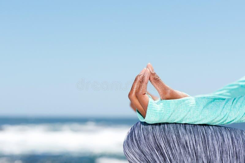 Manos femeninas de la yoga por el mar imagenes de archivo