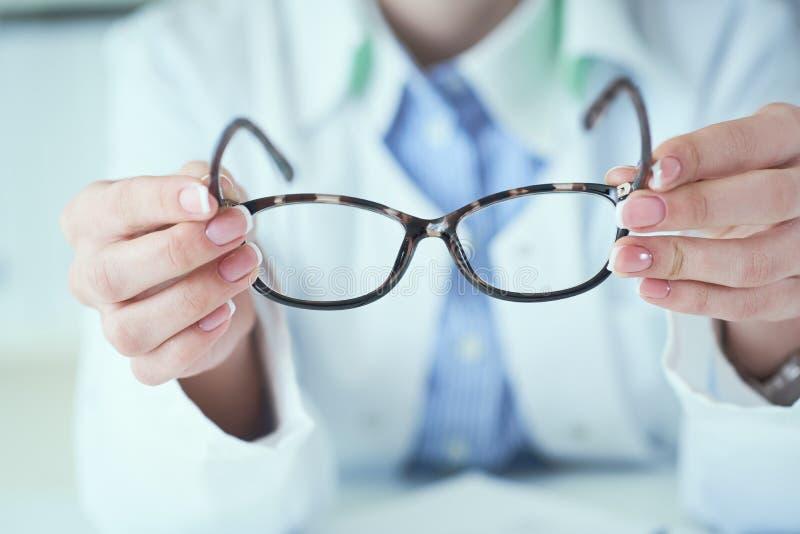 Manos femeninas del óptico que dan los nuevos vidrios al cliente para el primer de prueba y que intenta Oculista con comparar del fotos de archivo