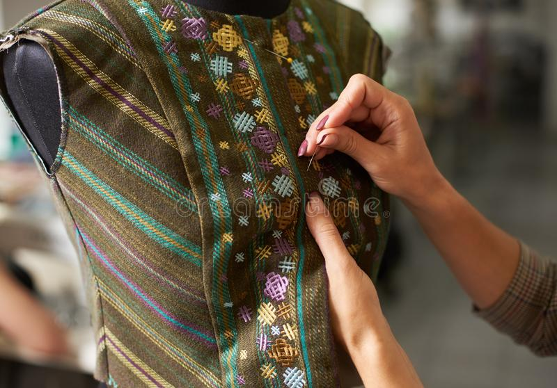Manos femeninas del diseñador con los pernos que caben la chaqueta en maniquí Estudio del sastre, empleo creativo foto de archivo libre de regalías