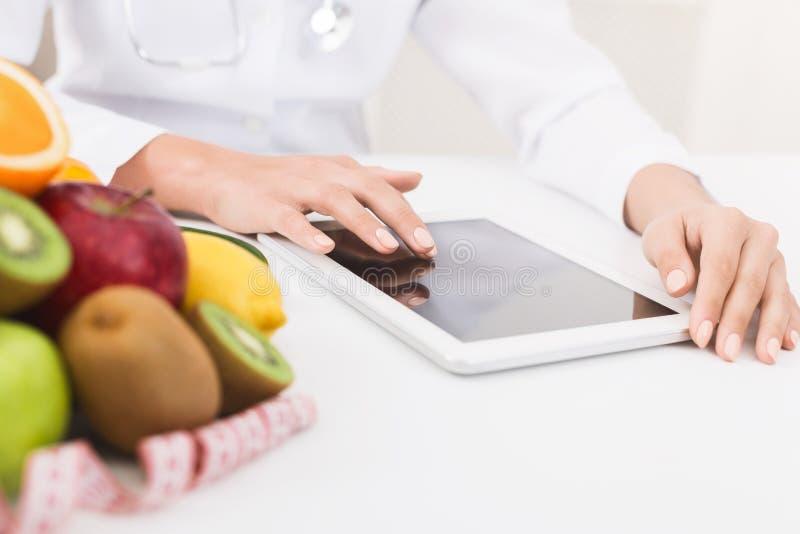 Manos femeninas del nutricionista que trabajan en la tableta digital en oficina imagenes de archivo
