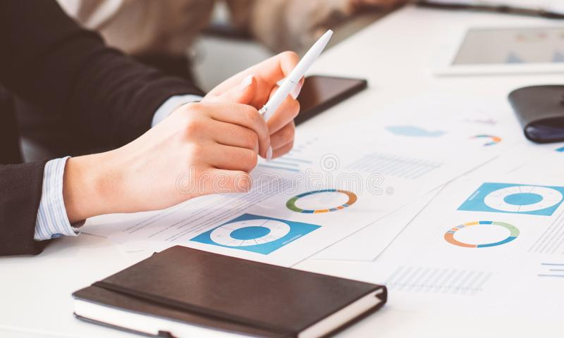 Manos femeninas del papeleo del análisis de la reunión de negocios imagen de archivo libre de regalías