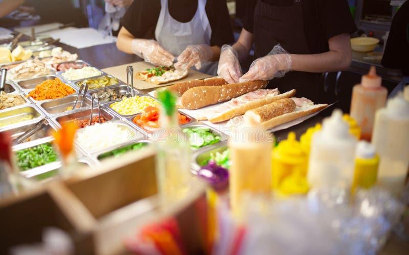 Manos femeninas del vendedor ambulante que hacen el bocadillo al aire libre bocados de la cocina, cocinando los alimentos de prep imagen de archivo