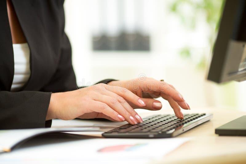 Manos femeninas en el teclado foto de archivo