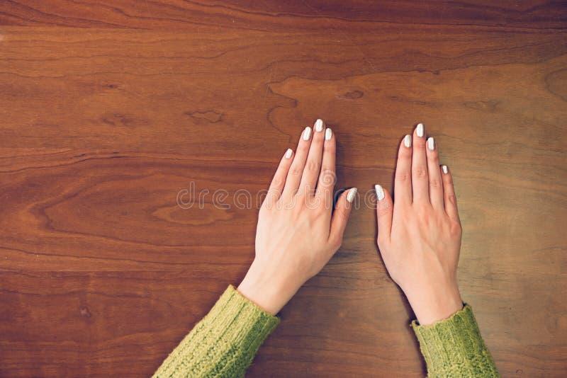 Manos femeninas en fondo de madera Vista a las manos femeninas de las palmas en la tabla del top imágenes de archivo libres de regalías