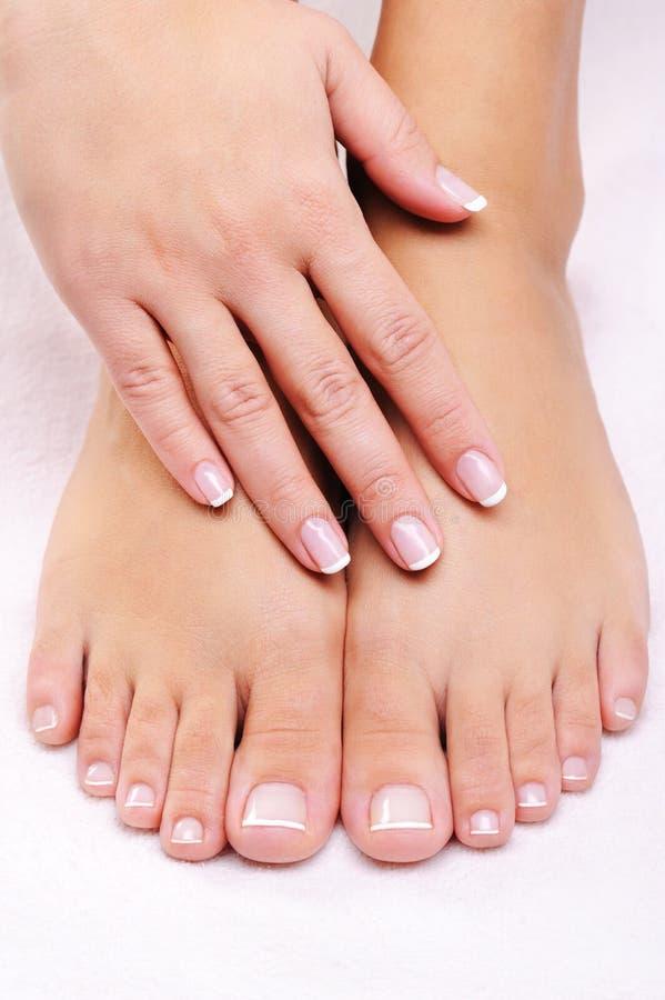 Manos femeninas en los pies well-groomed fotografía de archivo