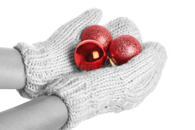Manos femeninas en manoplas con las bolas de la Navidad aisladas imágenes de archivo libres de regalías