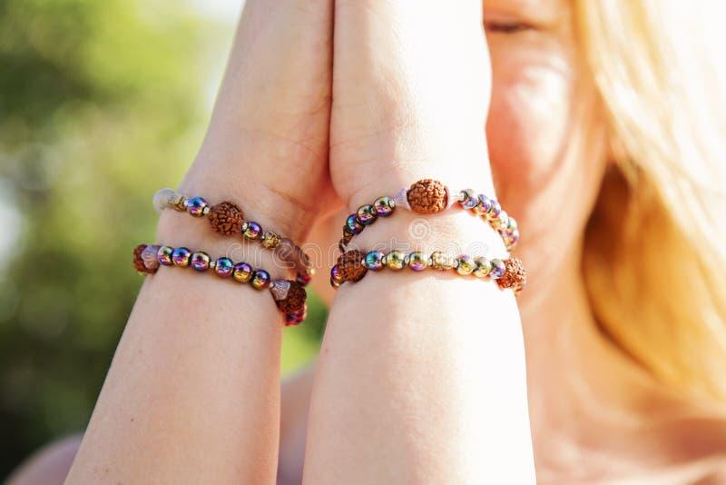 Manos femeninas en mudra del namaste con las pulseras foto de archivo