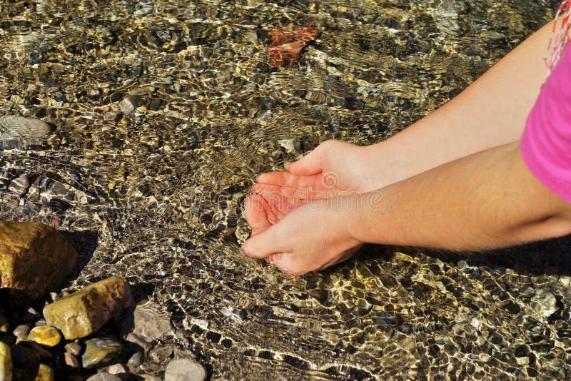 Manos femeninas en un río fotografía de archivo libre de regalías