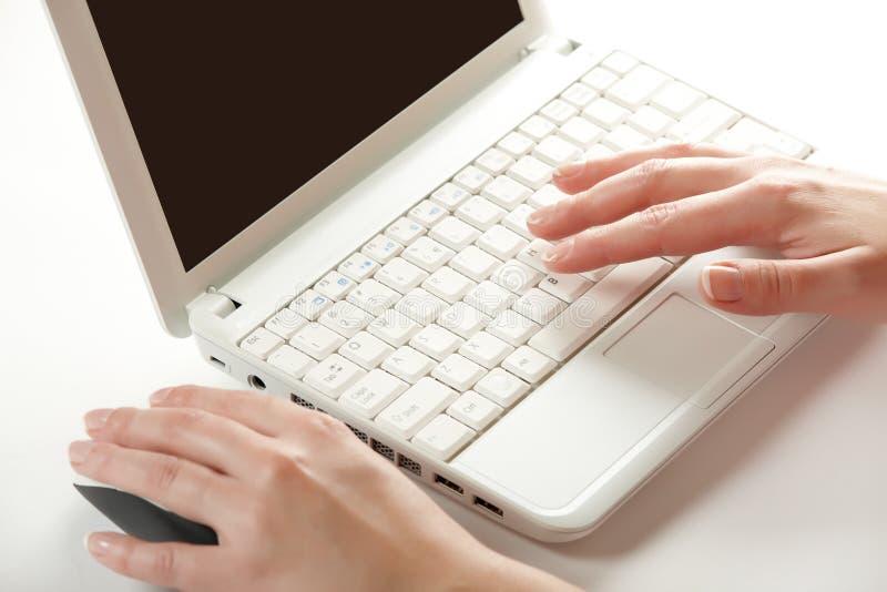 Manos femeninas en un teclado de la computadora portátil fotos de archivo libres de regalías