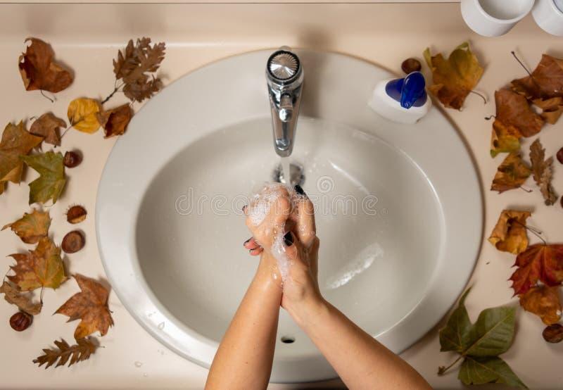 Manos femeninas haciendo burbujas de jabón por encima del fregadero fotos de archivo